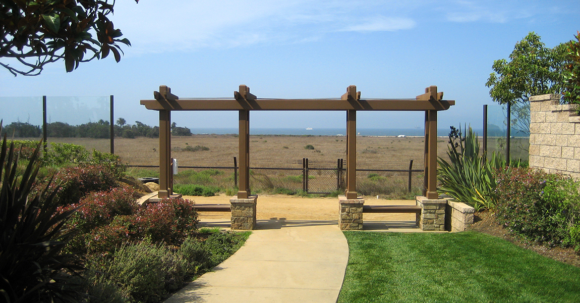 Pergola over drive way with open field and ocean in the background