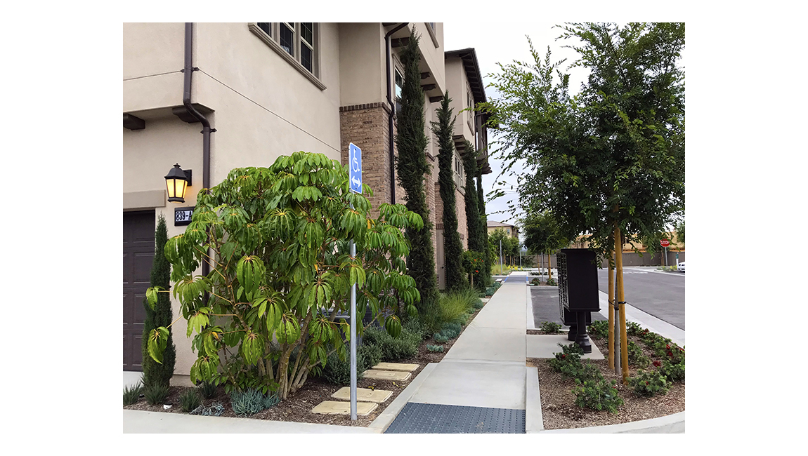 Two story building showing sidewalk and lush plants