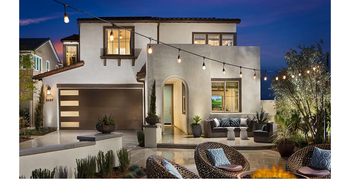 front of beige two story house with lawn furniture and lights